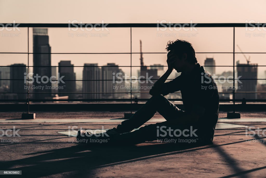 Silhouette of sad depressed Asian man lost hope and cry, sit on building rooftop at sunset, dark mood tone. Concept of major depressive disorder, friend zone, unemployment, stress emotion or paranoid stock photo