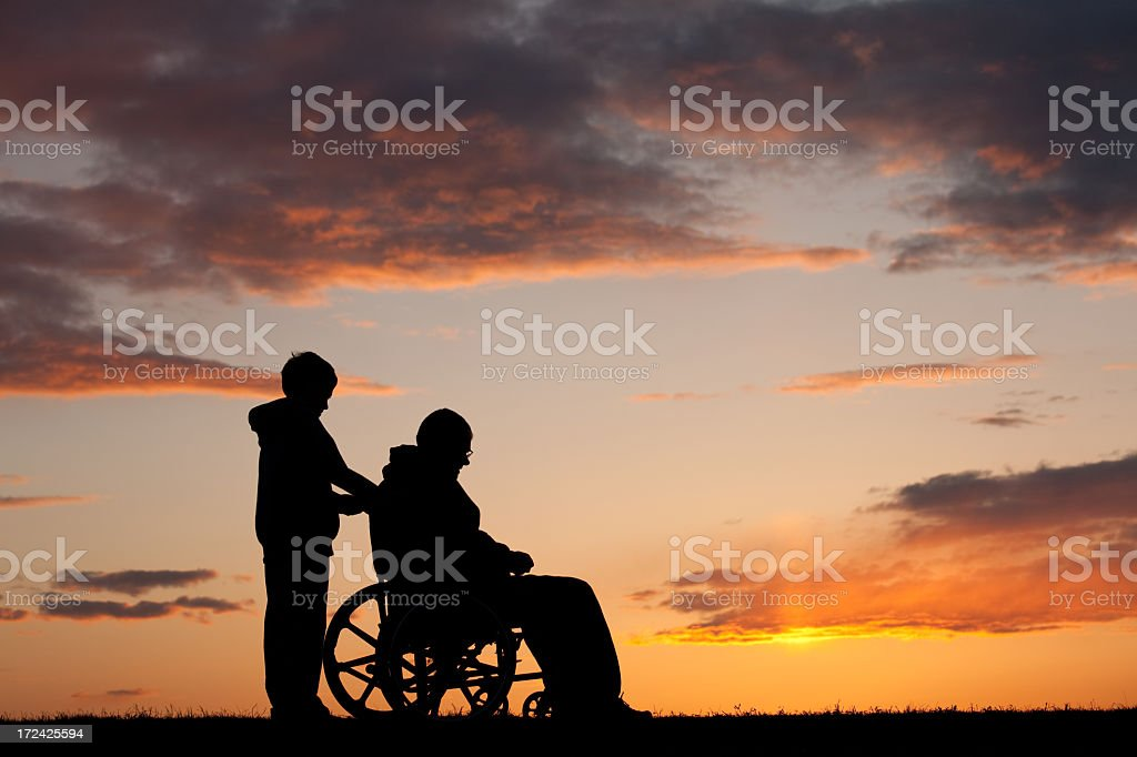 Silhouette of Sad Disabled Senior Man in a Wheelchair royalty-free stock photo