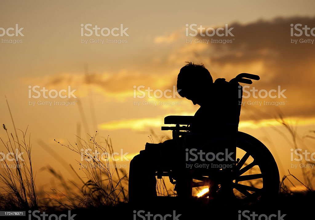 Silhouette of Sad Injured Boy in a Wheelchair stock photo