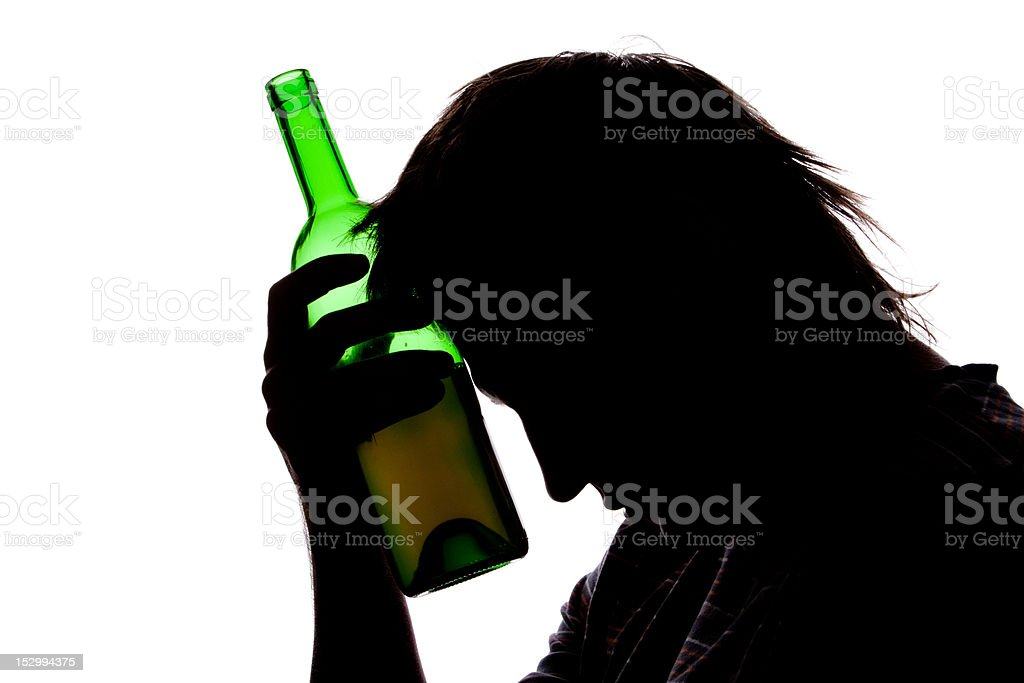 Silhouette of sad man drinking alcohol royalty-free stock photo