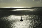 silhouette of sailboat on vast ocean