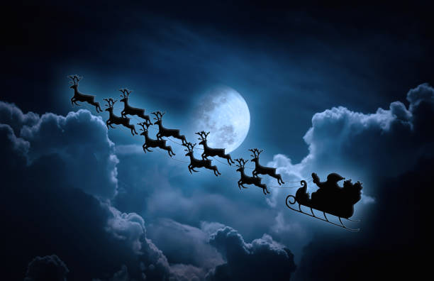 Silhouette of Santa Claus flying on sleigh pulled by reindeer. stock photo