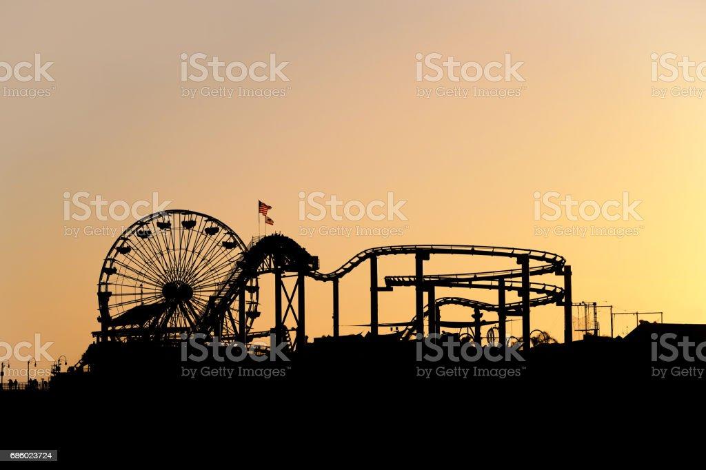 silhouette of santa monica pier amusement park with ferris wheel at sunset – Foto