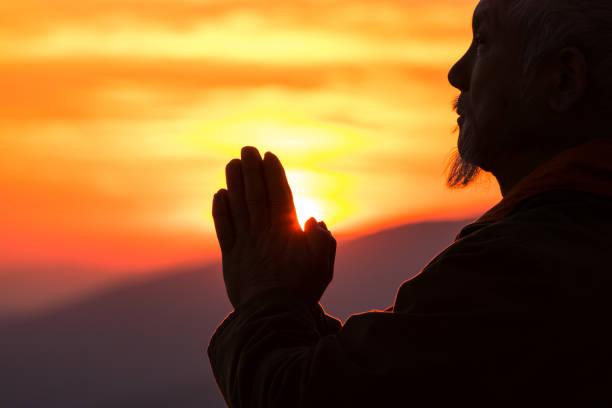 silhouette der senior asiatischen mann, der betet am oberen berg - gott sei dank stock-fotos und bilder