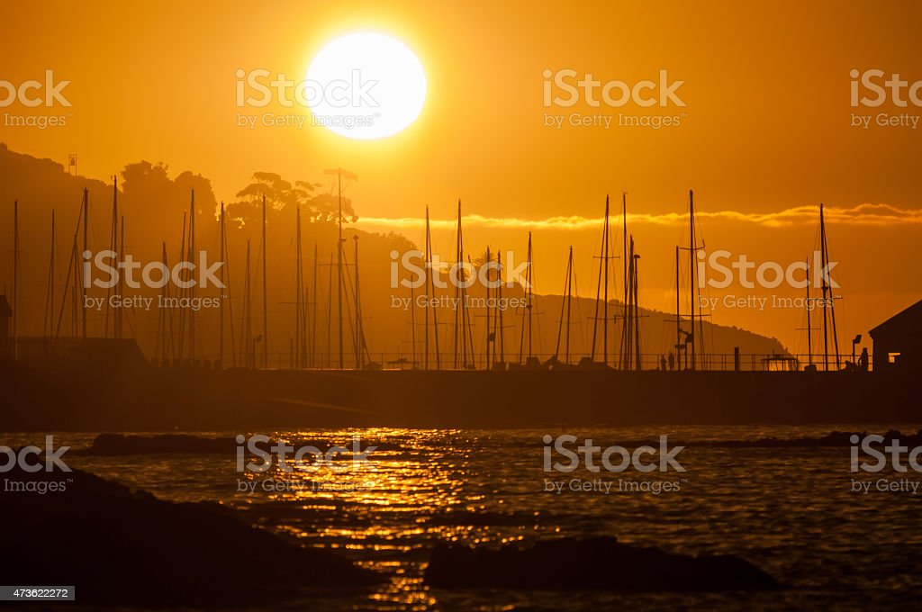 Silhouette of ships masts against sunset stock photo