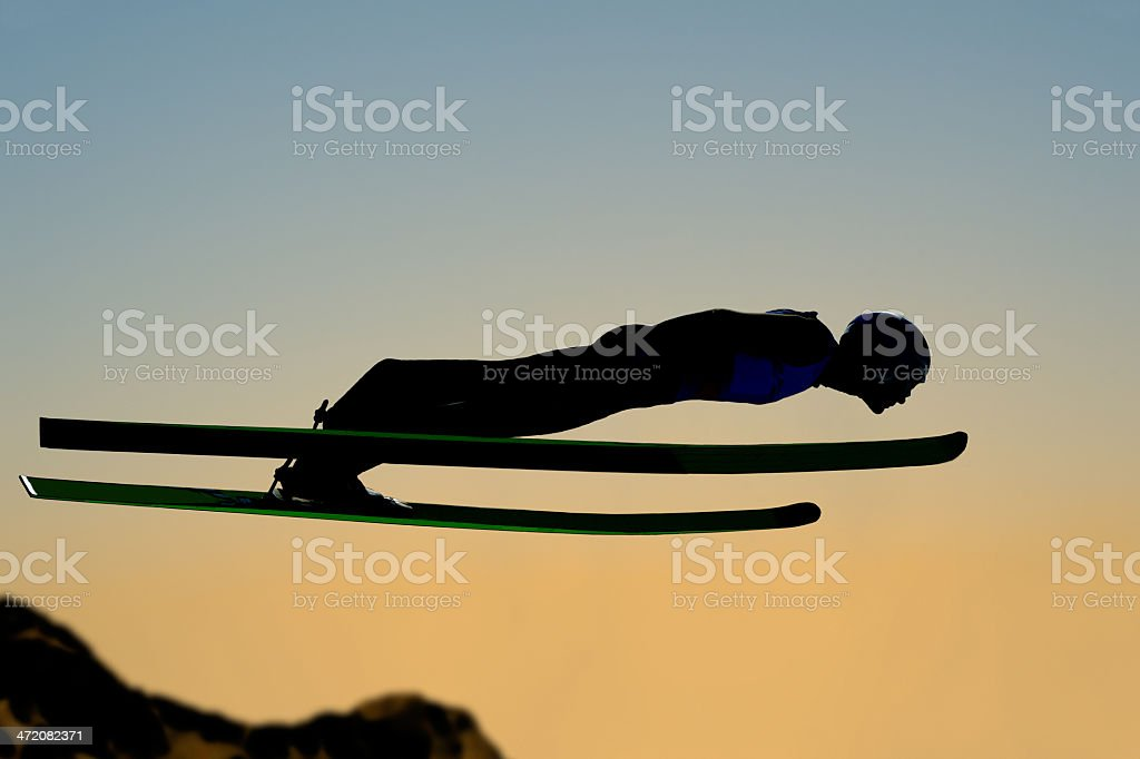 Silhouette of ski jumper flying at sunset stock photo