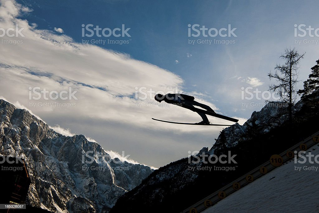 Silhouette of ski jumper in mid-air stock photo