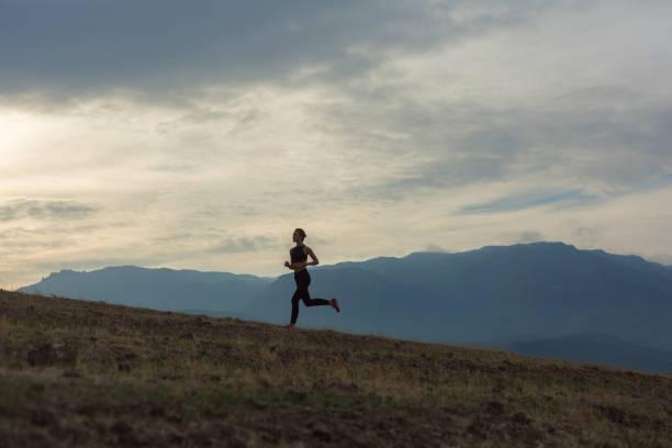 silhuetten av smal tjej jogging i dimmiga bergen - jogging hill bildbanksfoton och bilder