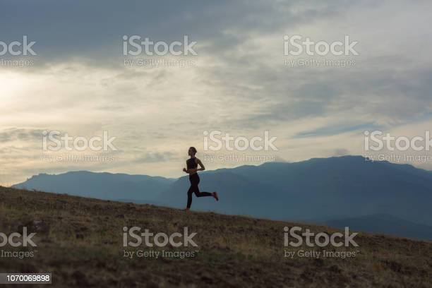 Photo of Silhouette of slim girl is jogging in foggy mountains