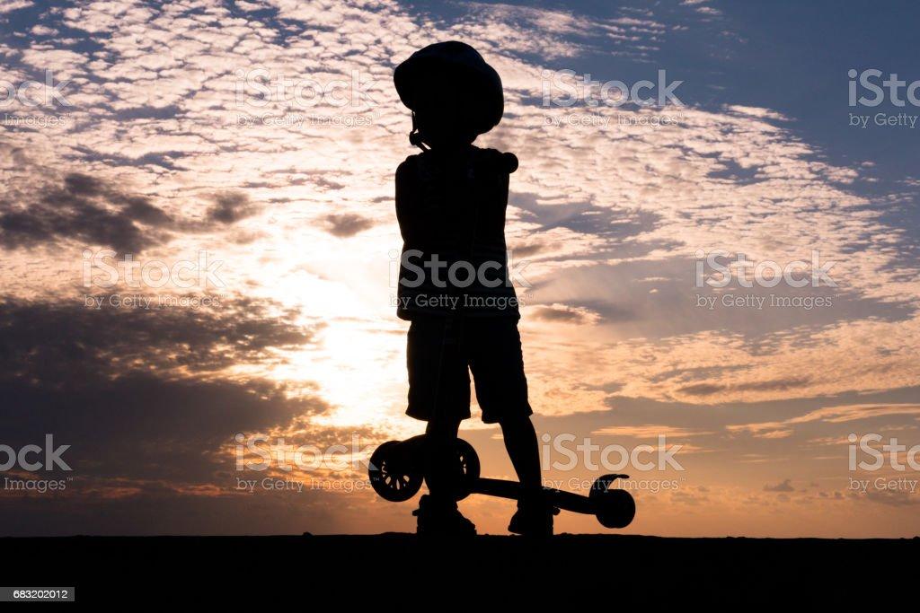 바다 일몰의 배경에 스쿠터와 헬멧을 착용 하는 작은 소년의 실루엣 royalty-free 스톡 사진
