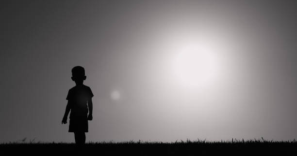 Silhouette of small child walking in a field. stock photo