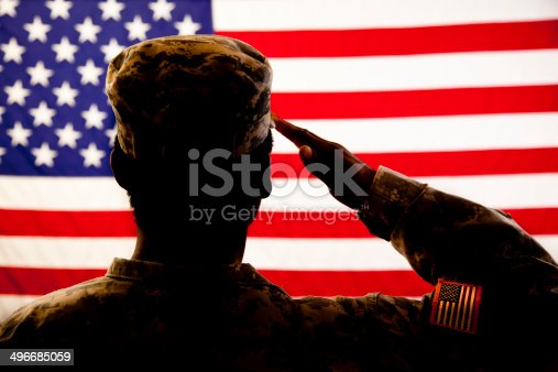 A military veteran salutes her American flag.  The patriotic veteran wears a military uniform, and she faces the flag with honor and respect.  The silhouette of the solider is shown against a red, white and blue flag background.  There is a flag patch on the sleeve of the woman's military uniform.