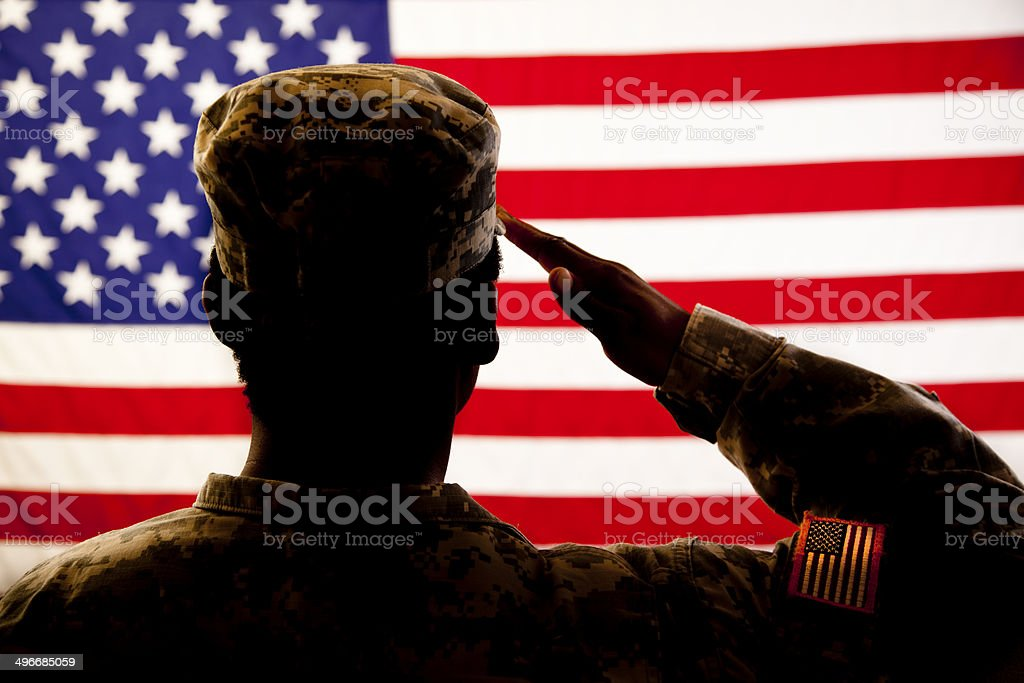 Silhouette of soldier saluting the American flag stock photo