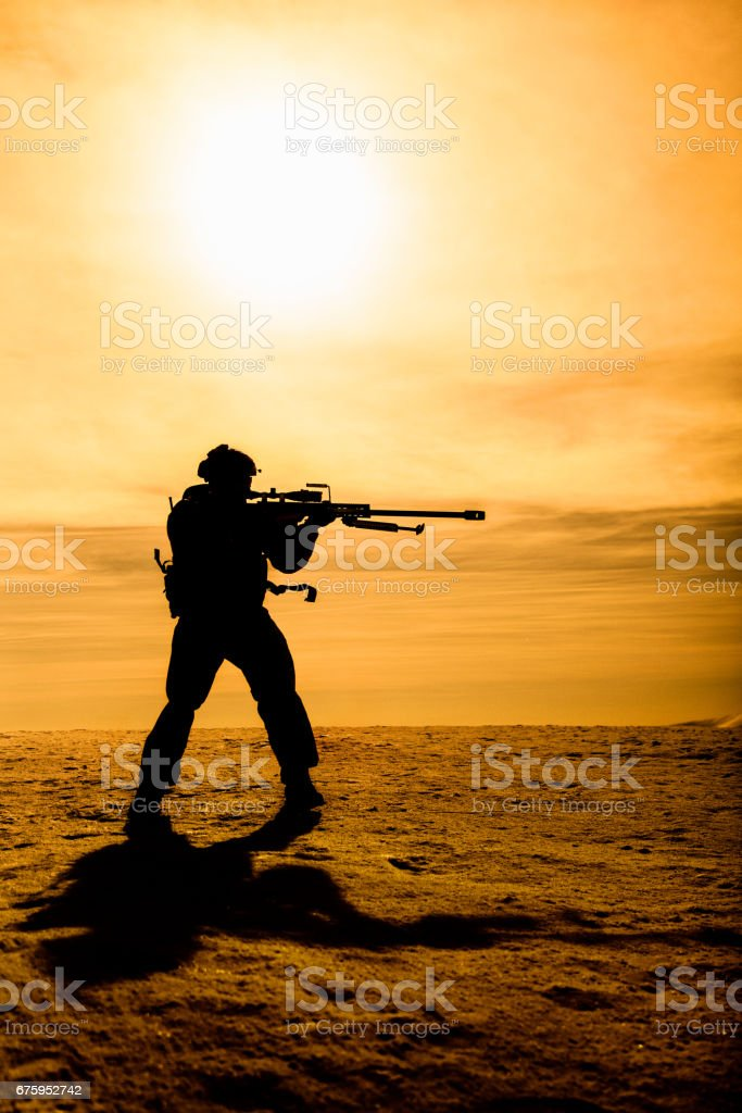Silhouette of soldier with sniper rifle stock photo