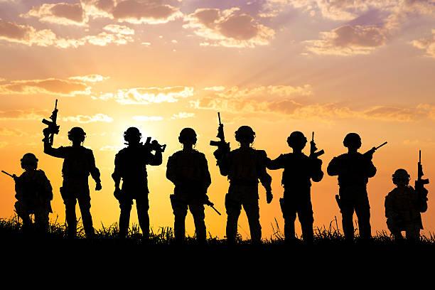 silueta de los soldados equipo con puesta de sol de fondo - personal militar fotografías e imágenes de stock