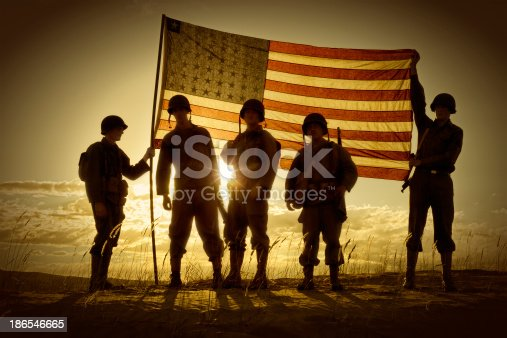 Four WWII Soldiers Holding up a translucent American Flag at sundown.  The sun  behind the flag creates a semi-silhouette of the four war weary soldiers.  Clouds, sun, and sand complete the picture.  All soldiers are in uniform with helmets and rifles, boots etc.