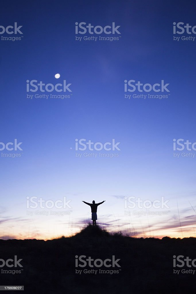 Silhouette of solitary male arms raised on beach at sunset royalty-free stock photo