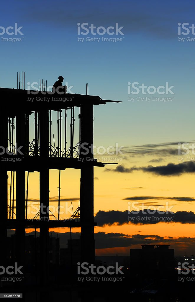 A silhouette of someone meditating at sunset stock photo