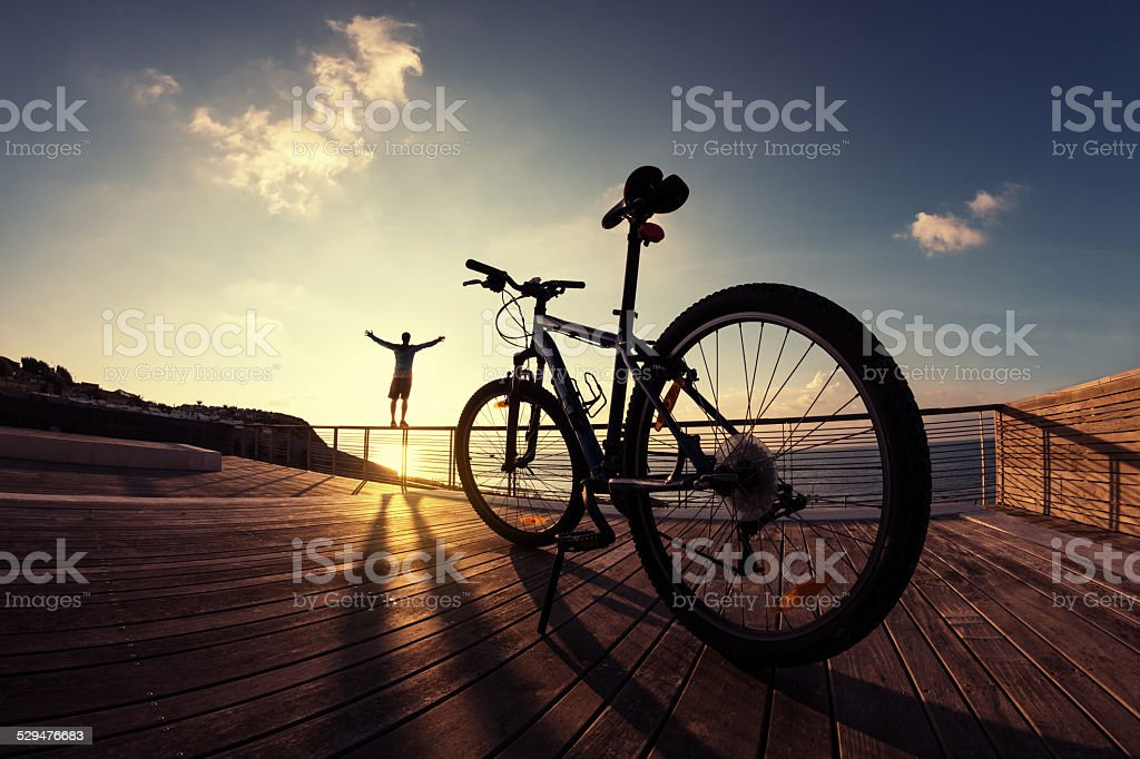 silhouette of sportsman and mountain bike at sunset stock photo