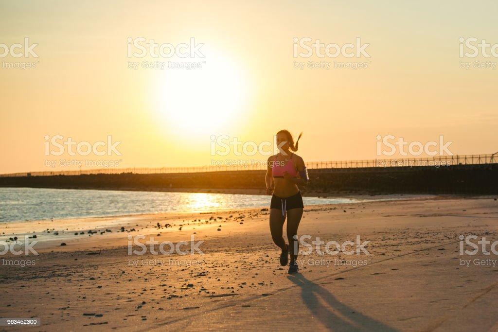 silhouette de sportive avec le smartphone en exécutant brassard jogging sur la plage contre les rayons du soleil - Photo de Activité libre de droits