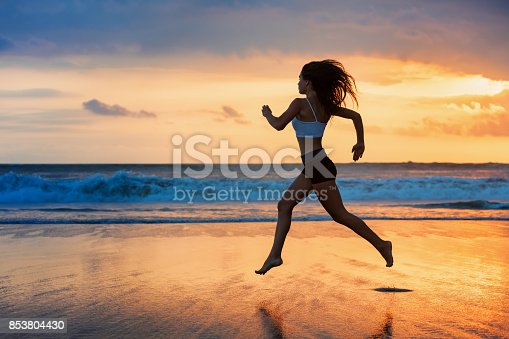 istock Silhouette of sporty girl running by beach sea surf pool 853804430