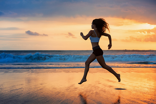 Silhouette of sporty girl running by beach sea surf pool
