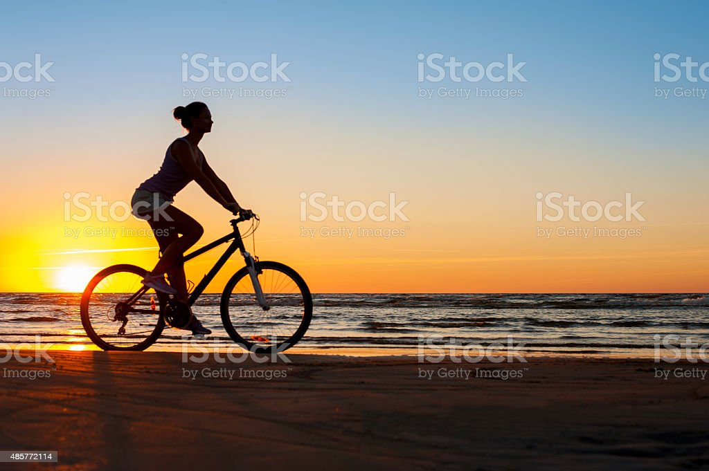 Silhouette of sporty woman riding bicycle on multicolored sunset background. stock photo
