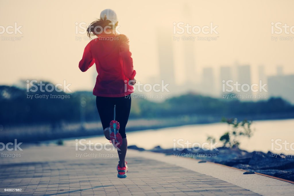 silhouette of sporty young fitness woman running on sunrise coast trail – zdjęcie