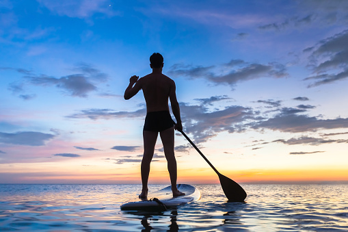 Silhouette of stand up paddle boarder paddling at sunset, sea