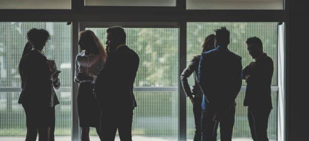 Silhouette der Geschäftsleute im Büro stehen – Foto