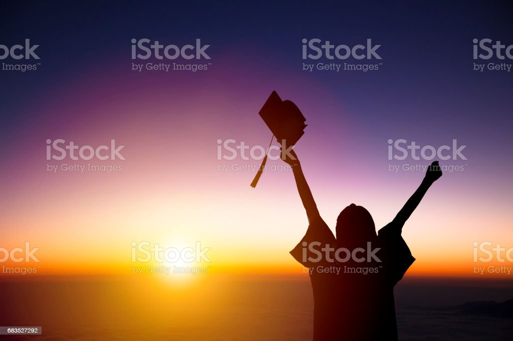 silhouette of Student Celebrating Graduation watching the sunlight stock photo