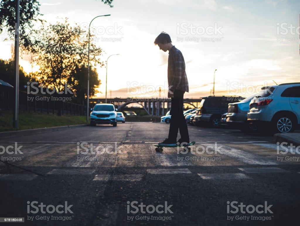 silhouette de l'homme élégant en tenue décontractée le skateboard de penny à cheval sur le passage pour piétons de la ville - Photo