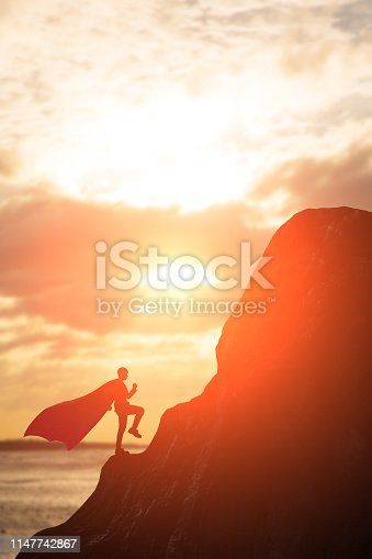 silhouette of super businessman with cape climb the montain in the sunset