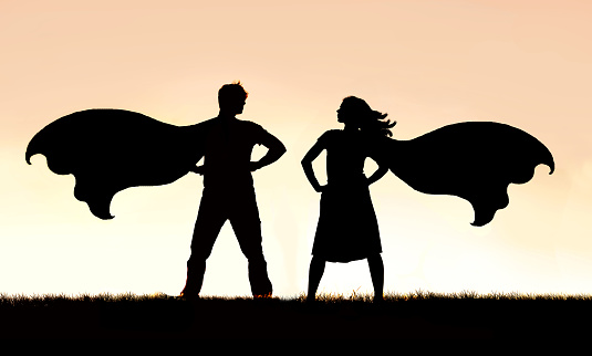 A silhouette of a superhero man and woman couple in capes standing strong and powerful against a sunset sky background.