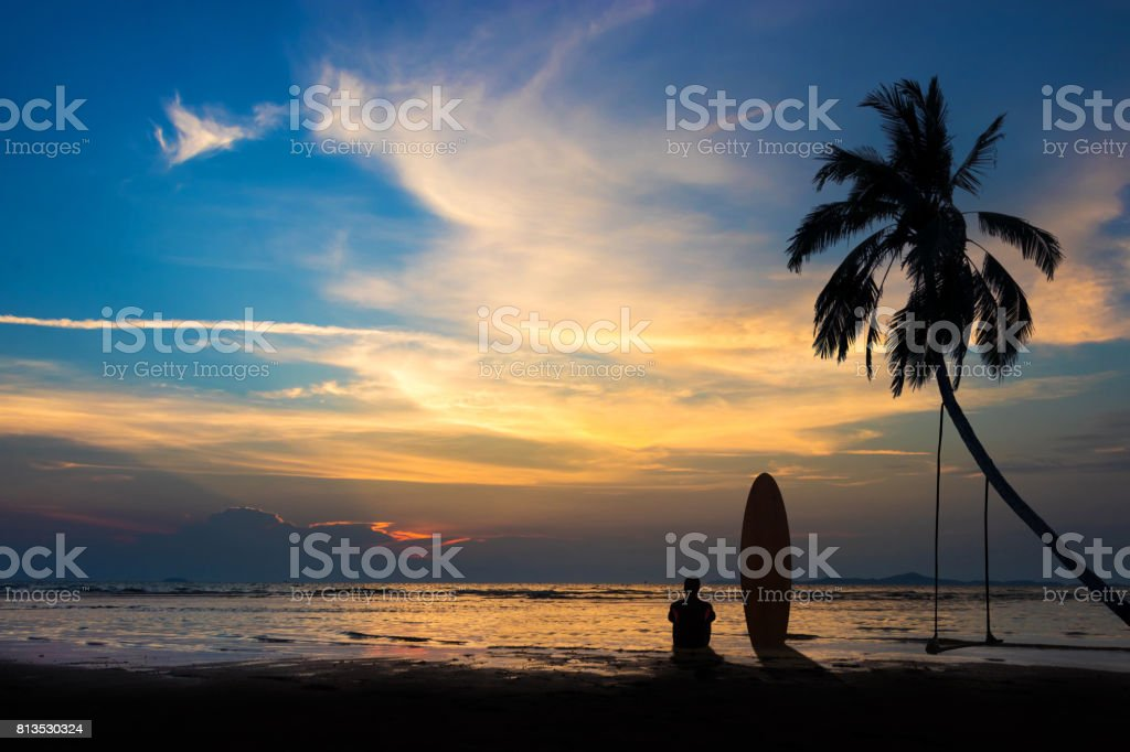Silhouette of surf man sit with a surfboard on the beach. Surfing scene at sunset beach with colorful sky. Outdoor water sport adventure lifestyle.Summer activity. Handsome Asia male model in his 20s. stock photo