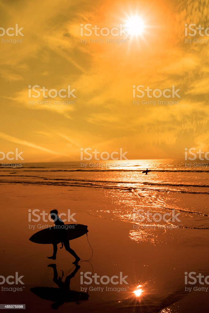 silhouette of surfer walking from the sea stock photo