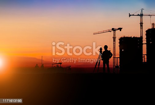 istock Silhouette of Survey Engineer and construction team working at site over blurred  industry background with Light fair.Create from multiple reference images together 1171613193