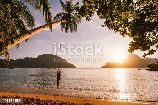Silhouette of swing men with sunset over tropical island in background. El Nido bay. Philippines.