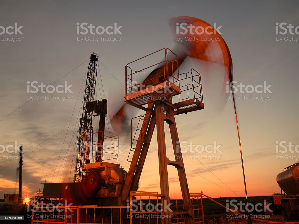 Silhouette of swinging oil pump in evening sky stock photo