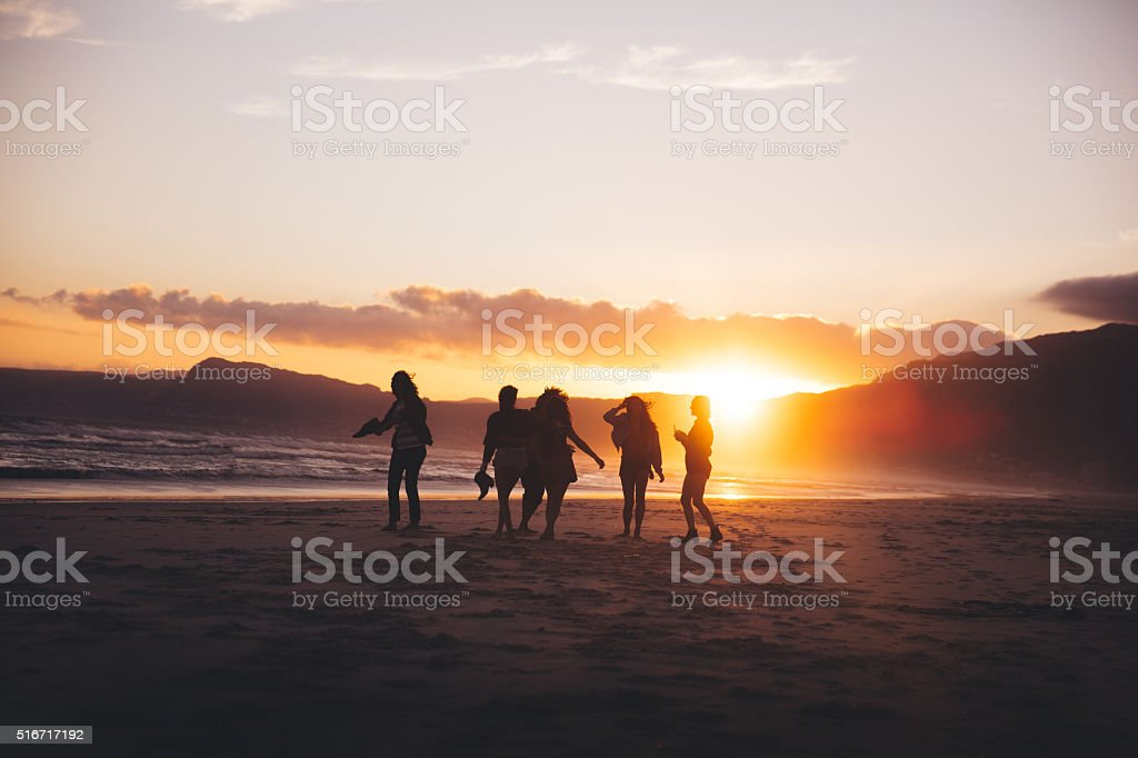 Silhouette of teen friends dancing on the beach at sunset foto