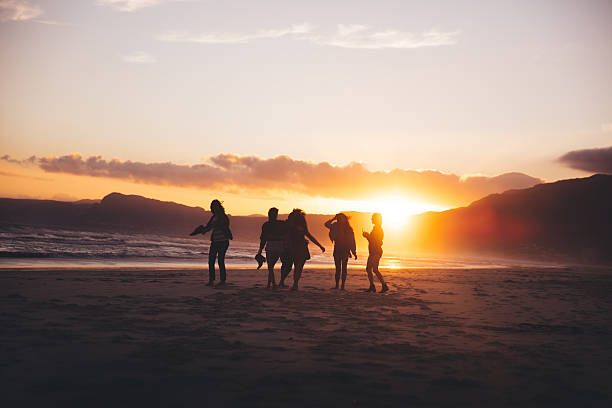 Silhouette of teen friends dancing on the beach at sunset stock photo