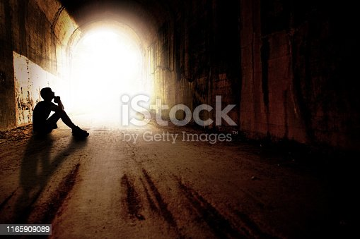 The silhouette of a teenage boy praying as he sits in a dark tunnel with bright light coming from the end of it.