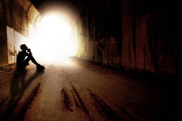 Silhouette of  Teen in Praying in Dark Tunnel stock photo