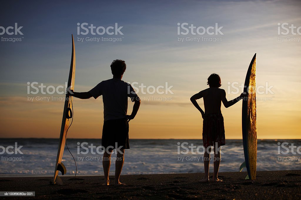 Silhouette of teenage boy (14-15) and father with surfboards on beach, rare view photo libre de droits