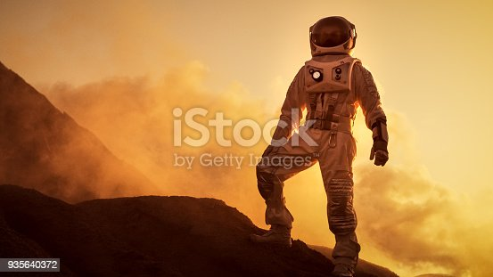 istock Silhouette of the Astronaut Standing on the Rocky Mountain of the Alien Red Planet/ Mars. First Manned Mission on Mars. Space Exploration, Colonization. 935640372