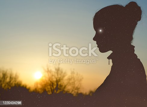 Silhouette of the beautiful woman in the nature at summer sunset.