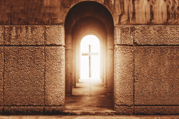 Silhouette of the cross at the end of tunnel with ray of sunlight behind stock photo