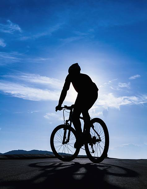Silhouette of the cyclist riding stock photo