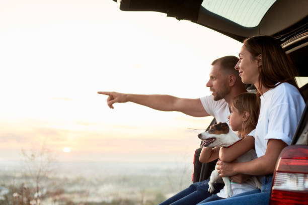 Silhouette of the family in a car trunk on the sunset Side view of the family sitting in the car trunk outside the city, watching the sunset, father is pointing on the horizon, copy space road trip stock pictures, royalty-free photos & images