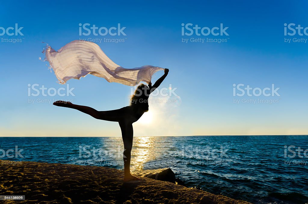 Silhouette of the happy woman with fiber dancing at sunset stock photo